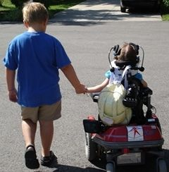 Two children walking; the younger child in the wheelchair has spinal muscular atrophy (SMA).